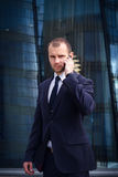 Businessman talking on his cellphone while walking outdoors. In front of a modern office building Royalty Free Stock Photos