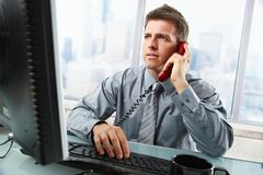 Businessman talking on landline phone in office. Determined businessman discussing computer work on landline phone while looking at screen typing on keyboard at Royalty Free Stock Photos
