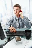 Businessman talking on landline phone in office. Determined businessman discussing computer work on landline phone while looking at screen typing on keyboard at Royalty Free Stock Image