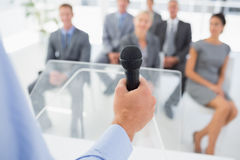 Businessman talking in microphone during conference Royalty Free Stock Image