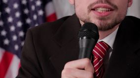 Businessman talking into the microphone. US flag, guy and microphone. Slight smile during speech. Story told by local politician stock video footage