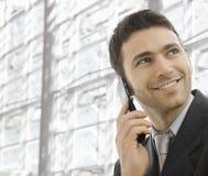 Businessman talking on mobile. Closeup portrait of happy businessman talking on mobile in front of office building windows Stock Photos