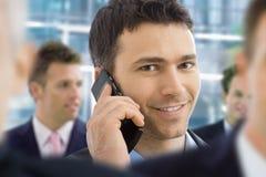 Businessman talking on mobile. Closeup portrait of happy businessman talking on mobile in crowd in office lobby Royalty Free Stock Photos