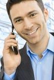 Businessman talking on mobile. Closeup portrait of happy businessman talking on mobile in front of office building windows Royalty Free Stock Image