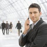 Businessman talking on mobile. Closeup portrait of happy businessman talking on mobile in front of office building windows Stock Image