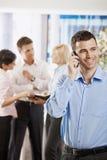 Businessman talking on mobile. Portrait of happy businessman talking on mobile phone in office Stock Images