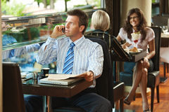 Businessman talking on mobile in cafe Royalty Free Stock Photos