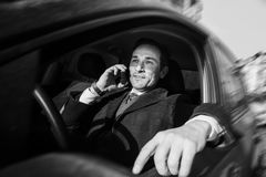 Businessman is talking on the mobile  in driver seat , day , outdoor Stock Photography