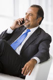 Businessman talking on mobile phone. In lobby Royalty Free Stock Image