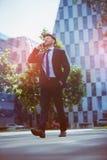Businessman talking on mobile phone against office building. Handsome businessman talking on mobile phone while walking on road stock photos