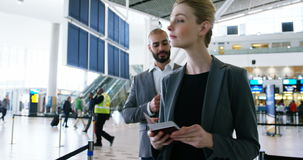 Businessman talking on mobile phone. And businesswoman checking her boarding pass at airport terminal stock video