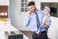 Businessman talking on mobile phone while carrying daughter Royalty Free Stock Photography