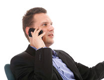 Businessman talking on mobile phone isolated. Confident mature man talking on his mobile phone isolated on white background Royalty Free Stock Image