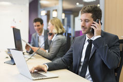 Businessman talking on the mobile phone in modern office Stock Photos