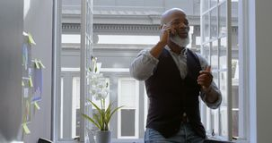 Businessman talking on mobile phone near window 4k. Businessman talking on mobile phone near window in office 4k stock footage
