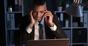 Businessman talking on mobile phone at night office. Businessman talking on mobile phone while working late night at office stock video