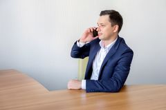 Businessman talking on mobile phone in office Royalty Free Stock Images