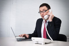 Businessman talking on mobile phone in office Royalty Free Stock Photography
