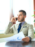 Businessman talking on mobile phone in office Stock Photo