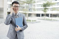 Businessman talking on mobile phone outdoors. Young Asian businessman in eyeglasses and in formal wear holding blue folder and talking on mobile phone in the stock photos