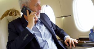Businessman talking on mobile phone in private jet 4k