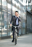 Businessman talking with mobile phone and riding a bicycle Royalty Free Stock Images