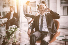 Businessman talking on mobile phone. While sitting on chair in office Royalty Free Stock Photos