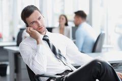 Businessman talking on mobile phone sitting near the desktop Stock Image