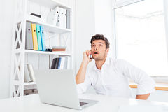 Businessman talking on mobile phone while sitting at office desk Stock Images