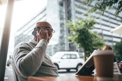 Businessman talking on mobile phone sitting at a restaurant. Businessman in sweater talking on cell phone while reading a book sitting at a restaurant with Royalty Free Stock Photography