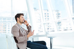 Businessman talking on mobile phone while sitting at the table Stock Photos