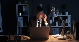 Businessman talking on mobile phone and using laptop at night. African american businessman talking on mobile phone and using laptop at night office stock footage
