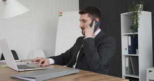 Businessman talking on mobile phone while working on laptop. Handsome businessman discussing on phone call while looking at laptop screen stock footage