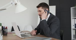 Businessman using laptop and mobile phone at office. Businessman talking mobile phone while working on laptop at office stock video