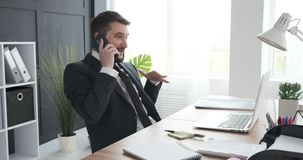 Businessman talking on mobile phone. Young businessman talking on mobile phone at workplace stock video footage
