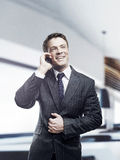 Businessman talking on mobile standing in office. Portrait of happy businessman talking on mobile standing in office, smiling Royalty Free Stock Image