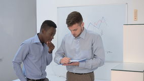 Businessman talking in office. Two businessman talking in office. African American businessman and Europeans to discuss the project and argue stock footage