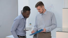 Businessman talking in office. Two young businessman talking in office. African American businessman and Europeans to discuss the project together stock video