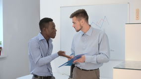 Businessman talking in office. Two young businessman talking in office. African American businessman and Europeans to discussing the price of the project stock footage