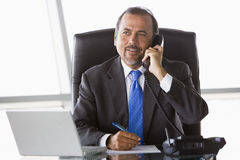 Businessman talking on phone. In office Stock Image