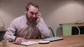 Businessman talking on the phone in a cafe stock video