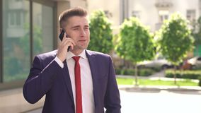Businessman talking on phone in city Park. stock video