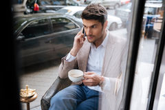 Businessman talking on the phone in a coffee shop Royalty Free Stock Image