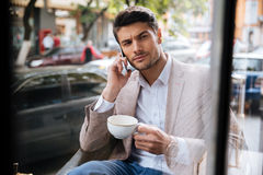 Businessman talking on the phone in a coffee shop Stock Photo