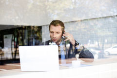 Businessman talking on phone in coffee shop Royalty Free Stock Photo