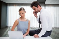 Composite image of businessman talking on phone while discussing with colleague over laptop against stock photos