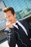 Businessman talking on the phone with earphones. Businessman talking on phone outside building Stock Image