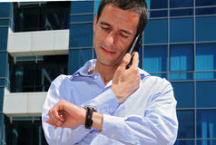 Businessman talking on the phone  in front of modern building. Businessman in a hurry looking at his watch Stock Images