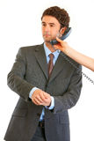 Businessman talking on phone in hand of secretary Stock Image
