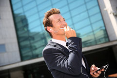 Businessman talking on the phone with handsfree set. Businessman talking on phone outside building Stock Photo